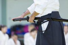 En manlig kampsportinstruktör med katana på seminarium arkivfoto
