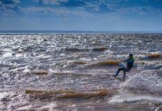 En manlig kiteboarder rider på ett bräde på en stor flod Han utför olika övningar, medan rörande på vatten Fotografering för Bildbyråer