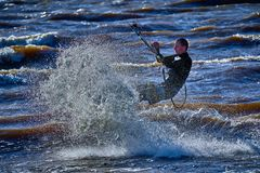 En manlig kiteboarder rider på ett bräde på en stor flod Han utför olika övningar, medan rörande på vatten Arkivbild