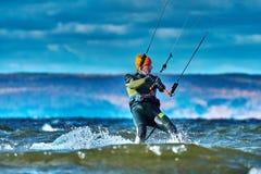 En manlig kiter glider på yttersidan av vattnet Färgstänk av vattenflugan ifrån varandra arkivbild