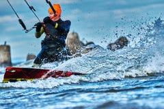 En manlig kiter glider på yttersidan av vattnet Färgstänk av vattenflugan ifrån varandra arkivbilder