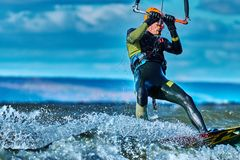 En manlig kiter glider på yttersidan av vattnet Färgstänk av vattenflugan ifrån varandra fotografering för bildbyråer