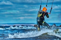 En manlig kiter glider på yttersidan av vattnet Färgstänk av vattenflugan ifrån varandra arkivfoton
