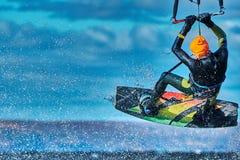 En manlig kiter hoppar över en stor sjö Närbild royaltyfri fotografi