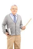 En manlig lärare som rymmer en trollstav och en bok Arkivfoto