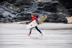 En manlig surfare som stöter ihop med stranden med surfingbrädan Royaltyfri Fotografi