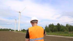 En manlig tekniker utför en kontroll och kontroll av en vindturbin som frambringar elektricitet, genom att rotera arkivfilmer