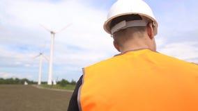 En manlig tekniker utför en kontroll och kontroll av en vindturbin som frambringar elektricitet, genom att rotera stock video