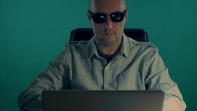 En manlig tjänsteman i en skjorta arbetar för en bärbar dator på natten man för mörka exponeringsglas Mannen klistrade minneslist stock video