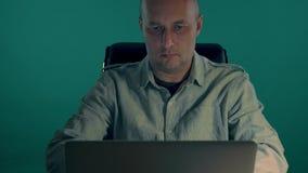 En manlig tjänsteman i en skjorta arbetar för en bärbar dator på natten Mannen klistrade minneslistan till bildskärmen Natt - arb stock video
