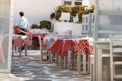 En manlig uppassare som på bär en tabell som förbereder restaurangen för kunder på en grekisk krog i Mykonos, Grekland arkivfoton