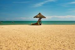 En manlivräddare som sitter under ett paraply av palmblad på en öde strand av den Hainan ön royaltyfri bild
