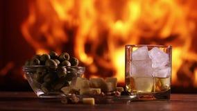 En mans hand häller whisky från en flaska in i ett exponeringsglas stock video