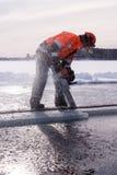 En mansawingis med en chainsaw på en djupfryst sjö i Savonlinna, Finland Arkivfoton