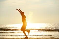En manspring på stranden med lyftta armar Arkivfoto
