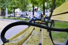 En manturist med ryggsäcken och mobiltelefonen vilar på en bänk i en stad parkerar fotografering för bildbyråer