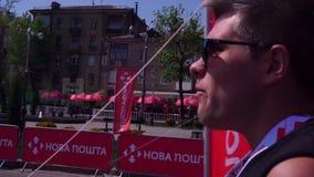 En maratondeltagare, en ung grabb, en idrottsman nen, i solglas?gon, n?r att ha k?rt som promenerar sp?ret, till och med staden lager videofilmer