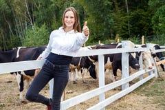 En marchant et ayez un temps d'amusement dans la ferme de lait La fille de bonheur manie maladroitement, regardant l'appareil-pho Photos libres de droits