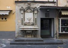 En marmorspringbrunn med den flätade ihop fisken som smyckar ett litet lager på en smal gata i Sorrento, Italien Royaltyfri Foto