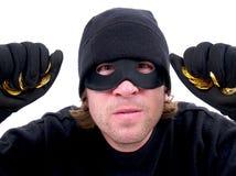 En maskerad brottsling med guld royaltyfri foto