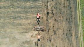 En maskin fungerar på en jordbruksmark som odlar jord, den bästa sikten arkivfilmer
