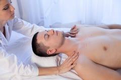 En massageterapeut gör en manhalsmassage i Spa royaltyfri fotografi