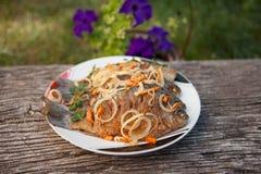 En maträtt av den stekte fisken på bakgrunden av den gamla trätabellen Arkivfoton