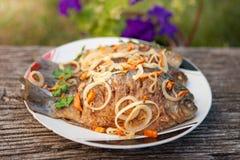 En maträtt av den stekte fisken på bakgrunden av den gamla trätabellen Arkivbild