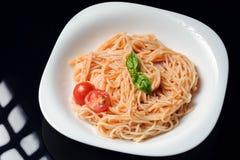 En maträtt av pasta i tomatsås i den vita plattan royaltyfria foton