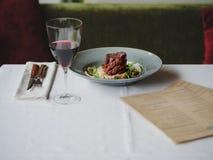 En matställesammansättning på en vit bordduk En platta med kötträtten, en matställeservice och ett exponeringsglas av vin på en s Arkivfoto