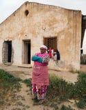 En medelålders Berberkvinna som framme står av hennes hus med ett utmanande uttryck på hennes framsida royaltyfri bild
