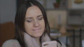 En medelålders kvinna använder telefonsammanträdet i ett kafé arkivfilmer