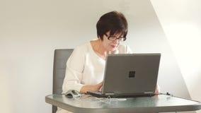 En medelålders kvinna arbetar concentratedly på datoren Hon är passionerad om arbete och talar till henne stock video