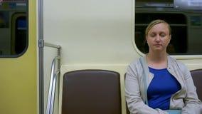 En medelålders kvinna faller sovande på gångtunnelen Trött kvinna Sitta i en gångtunnel arkivfilmer