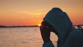 En medelålders kvinna i en huv som ber nära sjön på solnedgången Slapp fokus lager videofilmer