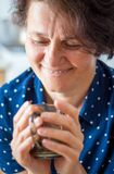 En medelålders kvinna i kafét rymmer en kopp av varmt te i hennes mummel arkivbild