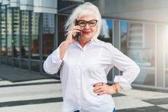 En medelålders kvinna, en iklädd pensionerad kvinna en vit skjorta och exponeringsglas, står på en stadsgata och talar på telefon Royaltyfri Foto