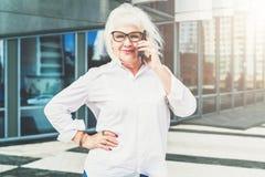 En medelålders kvinna, en iklädd pensionerad kvinna en vit skjorta och exponeringsglas, står på en stadsgata och talar på telefon Royaltyfria Foton