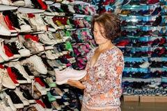En medelålders kvinna köper sportskor i en boutique_ arkivfoto