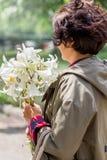 En medelålders kvinna med en bukett av vita liljor vita liljar royaltyfri bild