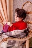 En medelålders kvinna sitter i en gungstol Kvinnahandarbete a så arkivfoto