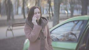 En medelålders kvinna som talar på telefonen nära bilen arkivfilmer