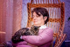 En medelålders kvinna sover i en gungstol med hennes favo royaltyfria foton