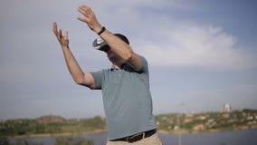 En medelålders man använder virtuell verklighetexponeringsglas i naturen arkivfilmer