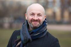 En medelålders man i en halsduk och ett omslag för en gå royaltyfri fotografi