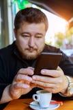 En medelålders man sitter i en coffee shop med en telefon Royaltyfri Fotografi