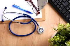 En medicinsk stetoskop nära en bärbar dator på ett trä Fotografering för Bildbyråer