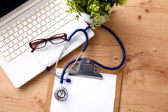 En medicinsk stetoskop nära en bärbar dator på ett trä Arkivfoton