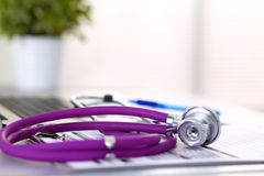 En medicinsk stetoskop nära en bärbar dator på ett trä Royaltyfria Bilder