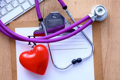 En medicinsk stetoskop nära en bärbar dator på ett trä Royaltyfria Foton